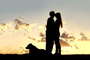 a silhouette of a married couple of man and woman share a loving hug and kiss at sunset with their German Shepherd Dog laying in the grass